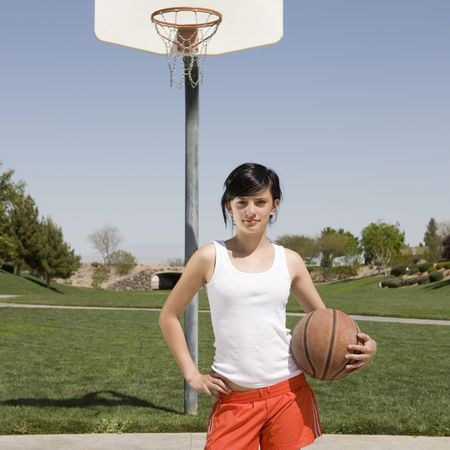 A teen hangs out at a basketball court
