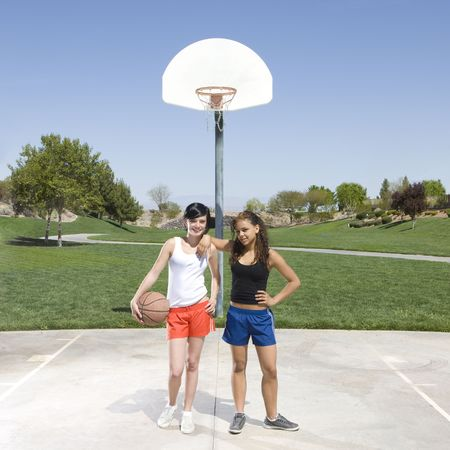 Two teens hang out at a basketball court