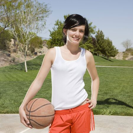 A teen girl with a basketball hangs out at a park photo