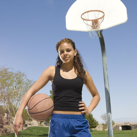 Teen girl with basketball hangs out at the park Stock Photo