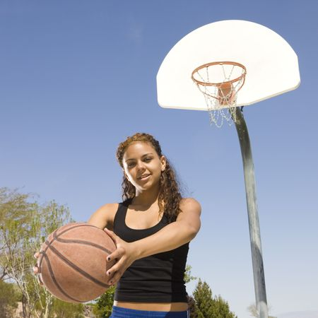 A teen with a basketball hangs out at the court