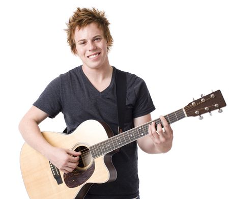 A boy smiles as he plays a guitar