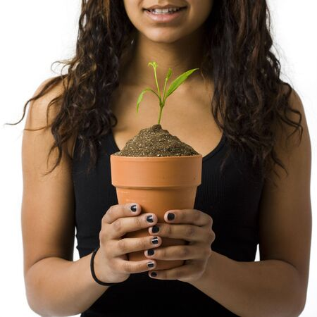 A girl with a potted plant smiles