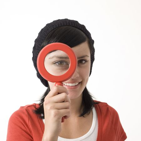 A girl holds up a magnifying glass to her eye photo