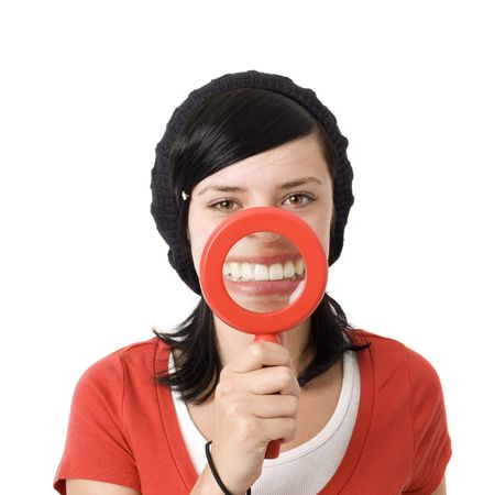 Girl shows teeth with magnifying glass