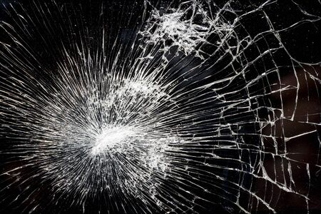 deflect: Abstract closeup shot of shattered glass. May have been struck by a bullet