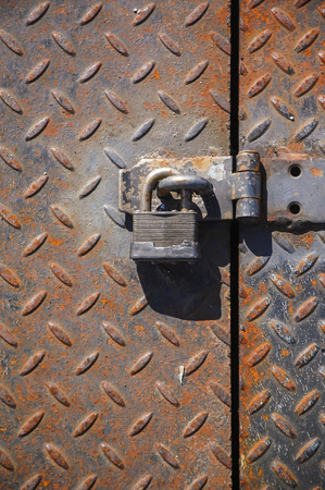 Grungy picture of a locked padlock against an iron door