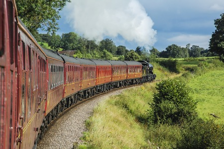 Shot taken out of the window of a train, showing a steam train pulling passenger cars Stock Photo
