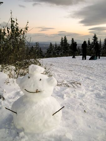 A snowman having a smoke behind a tree Stock Photo