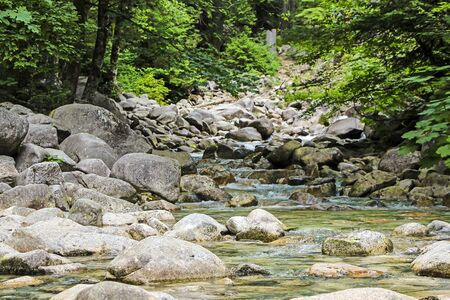 sooth: Peaceful scene with water flowing over rocks and stones Stock Photo