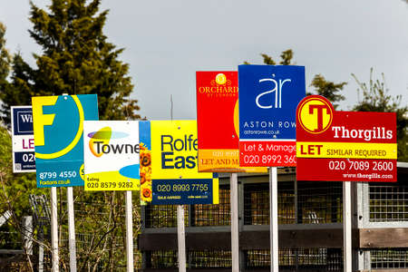 lettings: Multiple advertised boards from different estate agents outside a property Editorial
