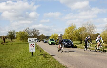 speeding: RIchmond Park, UK - April 2015: Cyclists in richmond park. A speeding ticket was recently issued to a cyclist in the park for not obeying the 20 mph speed limit sign.