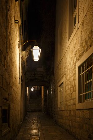 dimly: A dimly lit alley at night, could be from medieval times Stock Photo
