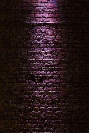 Shot of a brick wall texture illuminated with a purple light