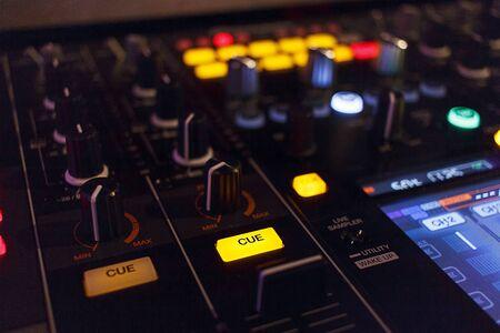 Résumé Angle d'une table de mixage DJ avec le bouton 'Cue' in focus