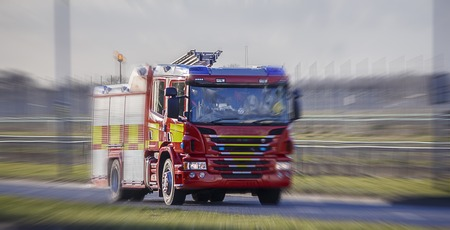 Fire Engine speeding to a call. Blurry background to illustrate urgency Standard-Bild