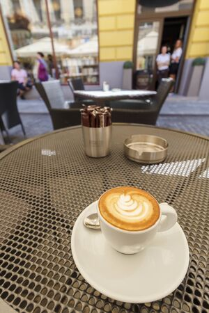 caffiene: A cup of coffee on a table at an outdoor cafe
