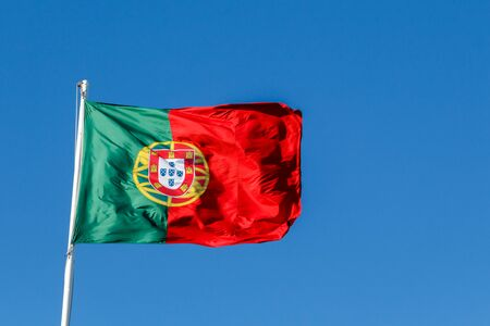Portugal flag blowing in the wind on blue sky background