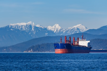 Cargo Ship with hills and mountains in the background Reklamní fotografie