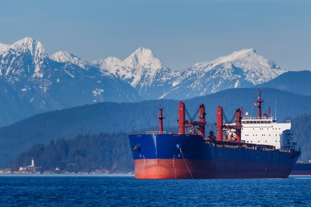 Cargo Ship with hills and mountains in the background 版權商用圖片