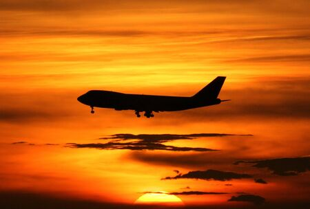business class travel: Airplane landing with beautiful sunset