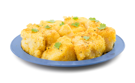 Indian Street Food Khaman Dhokla is a Food Common in The Gujarat State of India Made From Soaked And Freshly Ground Channa Dal or Channa Flour isolated on White Background