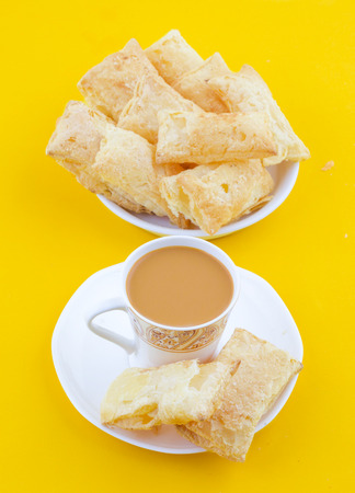 Indian Tea Time Breakfast Khari Also Know as Kharee, Khari Biscuit or Salty Puff Pastry Snacks, Served with Indian Hot Masala Chai or Hot Tea on Yellow Background