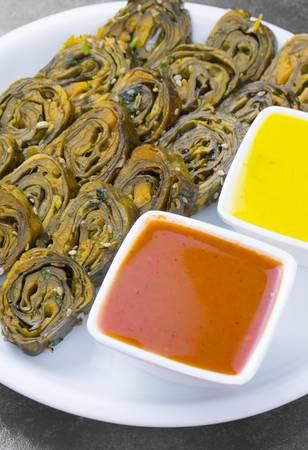 La nourriture épicée indienne Patra, également appelée Paatra, Alu Vadi ou Patrode, est un plat végétarien du Maharashtra ou de la cuisine gujarati. Il est fabriqué à partir de feuilles de colocasia farcies de farine de riz et d'épices, de tamarin, de jagré