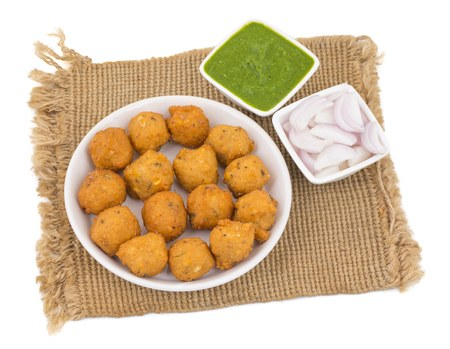 Indian Spicy Street Food Dal Vada Also Know as Moong Dal Vada, Pakoda, Pakode, Pakore, Moong Vada, Pakora or Bhajiya Served with Green Chutney or Onion isolated on White Background