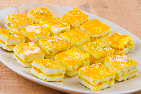 Paneer Burfi or Paneer Kesar Burfi is a Traditional Indian Mithai or Sweet Dish Prepared From Freshly Made Paneer, Mawa, Milk or Cottage Cheese on Wooden Background Stock Photo