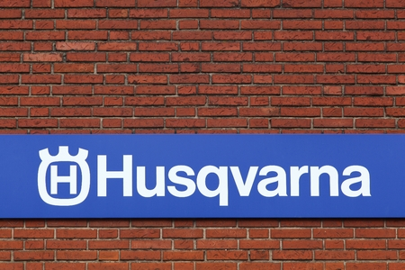 trimmers: Horsens, Denmark - September 3, 2015: Husqvarna  logo on a facade.  Husqvarna is swedish a manufacturer of robotic mowers, garden tractors, chainsaws, trimmers, bicycles and motorcycles