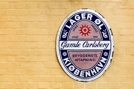 carlsberg: Viborg, Denmark - September 10, 2015: Old advertising of Carlsberg on a wall of a restaurant. Carlsberg Group is a danish brewing company founded in 1847 with headquarters located in Copenhagen