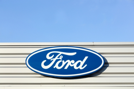 automaker: Belleville, France - September 20, 2015: Ford logo on a facade of a dealer. Ford is an American multinational automaker headquartered in Dearborn, Michigan, USA.