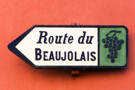Road of Beaujolais sign on red wall, France Stock Photo