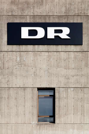 dr: Aarhus, Denmark - November 8, 2015: DR logo on the facade of radio and television studios in Aarhus. Danmarks Radio, abbreviated DR is the danish public broadcasting company founded in 1925 Editorial