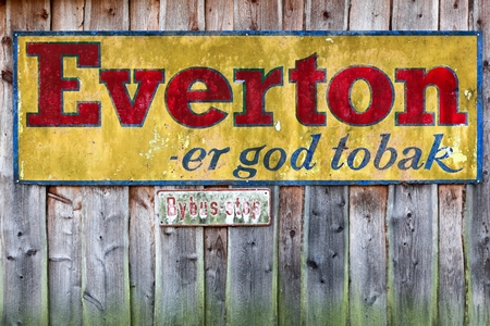 qui: Vejle, Denmark - November 12, 2015: Old Tobacco advertising of Everton on a wooden wall.Everton belong to Scandinavian Tobacco Group qui is the Worlds Largest manufacturer of cigars and pipe tobacco Editorial