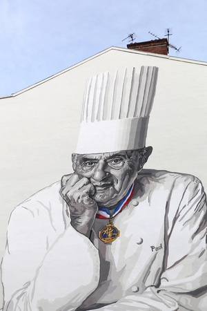culinary tourism: Lyon, France - January 27, 2016: Facade in Lyon with Paul Bocuse portrait. Paul Bocuse, 3 stars at the Michelin guide, is a french chef based in Lyon who is famous for the high quality of his restaurant Editorial