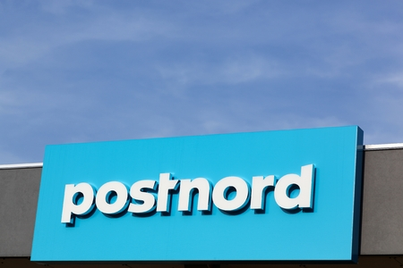 esbjerg: Esbjerg, Denmark - May 6, 2016: Postnord logo on a wall. PostNord is the name of the holding company of the two merged postal companies Posten AB and Post Danmark that were officially merged in 2009 Editorial
