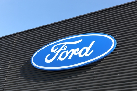 headquartered: Skanderborg, Denmark - May 5, 2016: Ford logo on a wall. Ford is an American multinational automaker headquartered in Dearborn, Michigan, USA Editorial