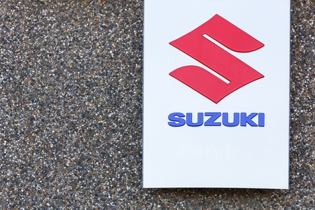 specializes: Skanderborg, Denmark - May 5, 2016: Suzuki logo on a wall. Suzuki is a Japanese multinational corporation headquartered in Japan which specializes in manufacturing automobiles, four-wheel drive vehicles, motorcycles, all-terrain vehicles Editorial