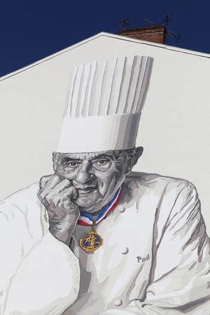 Lyon, France - March 26, 2016: Facade in Lyon with Paul Bocuse portrait. Paul Bocuse, 3 stars at the Michelin guide, is a french chef based in Lyon who is famous for the high quality of his restaurant