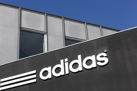 adidas: Aarhus, Denmark - May 1, 2016: Adidas logo on a wall. Adidas is a German multinational that manufactures sports shoes, clothing. It is the second biggest sportswear manufacturer in the world