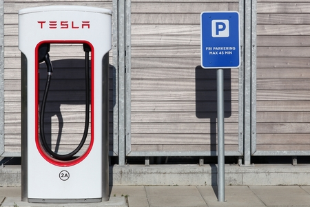 parking station: Aabenraa, Denmark - June 4, 2016: Tesla supercharger station and parking. Tesla is an American automotive and energy storage company that designs, manufactures, and sells luxury electric cars