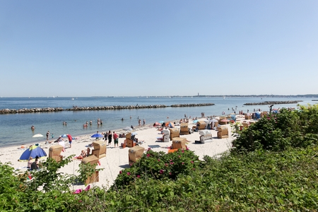 kiel fjord: Kiel, Germany - June 4, 2016: Schilksee beach surrounding the Kiel fjord with typical hooded chairs Editorial