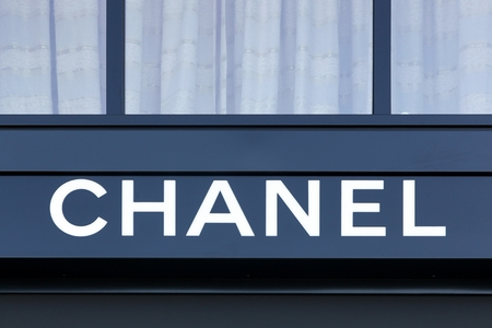 haute couture: Geneva, Switzerland - August 14, 2016: Chanel logo on a wall. Chanel is a French high fashion house that specializes in haute couture and ready-to-wear clothes, luxury goods and fashion accessories