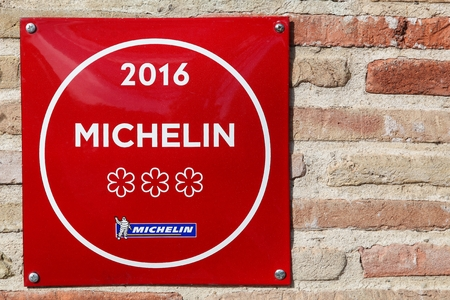 Vonnas, France - February 23, 2017: Michelin restaurant 3 stars symbol on a wall. Michelin guides are a series of guide books published by the French company Michelin for more than a century Editorial