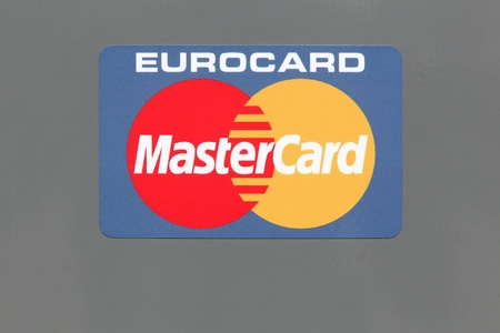 headquartered: Hvide Sande, Denmark - August 1, 2017: Logo of Mastercard on a panel. Mastercard is an American multinational financial services corporation headquartered in the MasterCard International Global