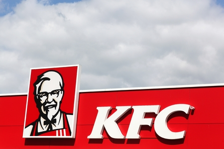 Holdorf, Germany - July 2, 2017: KFC logo on a wall. KFC is a fast food restaurant chain that specializes in fried chicken and is headquartered in Louisville, Kentucky, in the United States