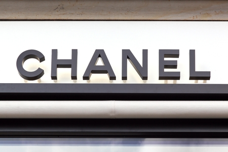 Copenhagen, Denmark - August 26, 2018: Chanel logo on a wall. Chanel is a French high fashion house that specializes in haute couture and ready-to-wear clothes, luxury goods and fashion accessories