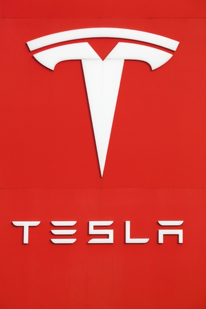 Tilst, Denmark - October 7, 2018: Tesla logo on a wall. Tesla is an American automotive and energy storage company that designs, manufactures, and sells luxury electric cars Editorial
